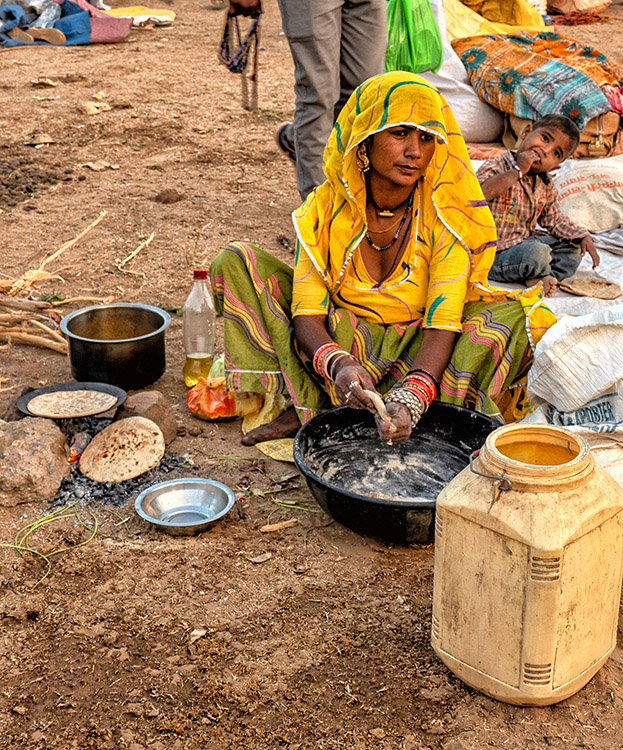 This beautiful young woman cooks on the ground while her toddler son eats at the Pushkar Camel Festival.