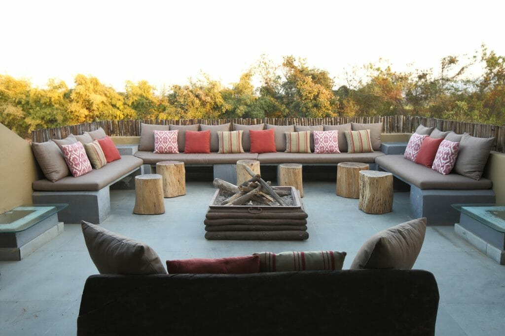 Outdoor fireplace surrounded by couches at Forsyth Lodge at Satpura National Park