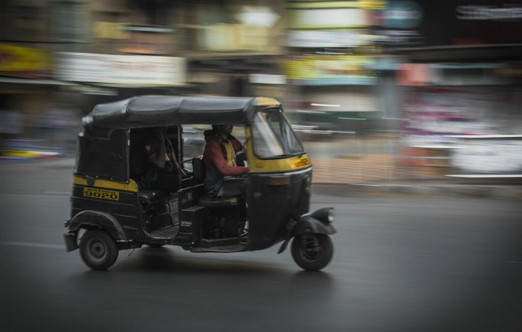 Black/Yellow Auto Rickshaw in India going at fast speed