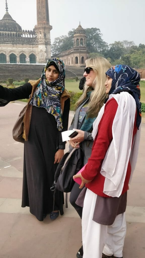 Two indian women in shawls and dresses taking a selfie with blonde white woman