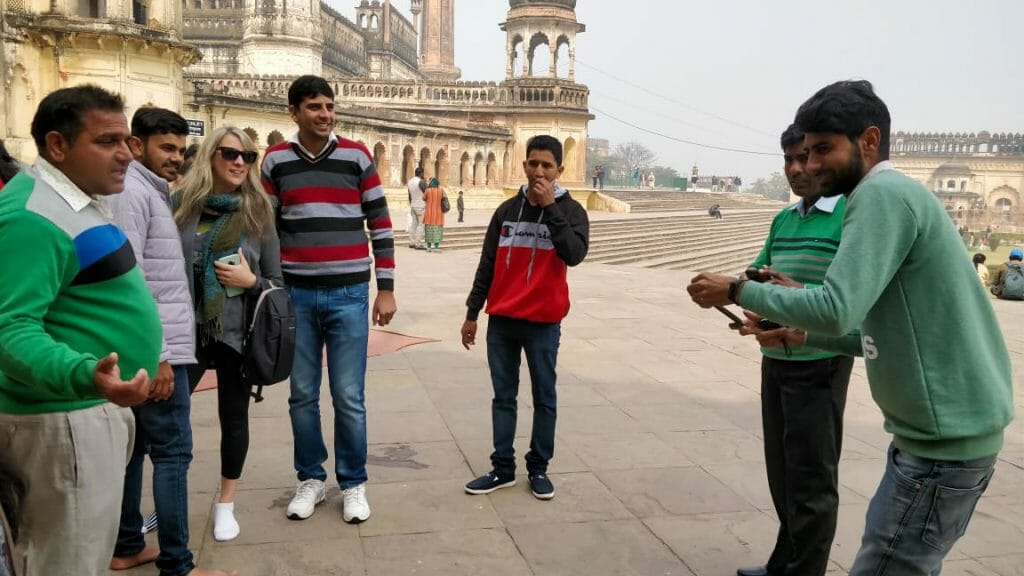 Group of Indian men taking a photo with a white woman