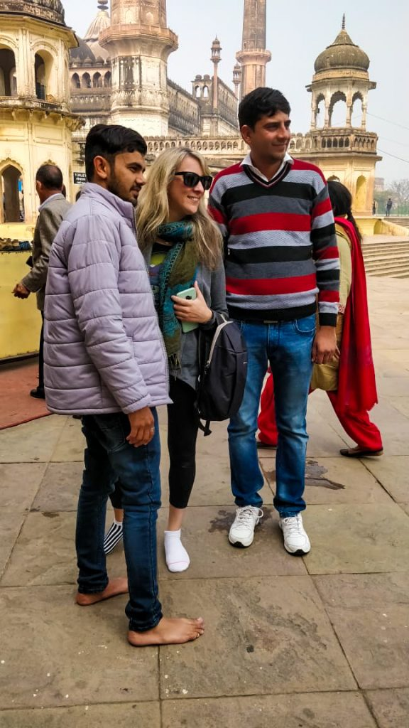 Two indian men taking a photo with a blonde white woman in the street