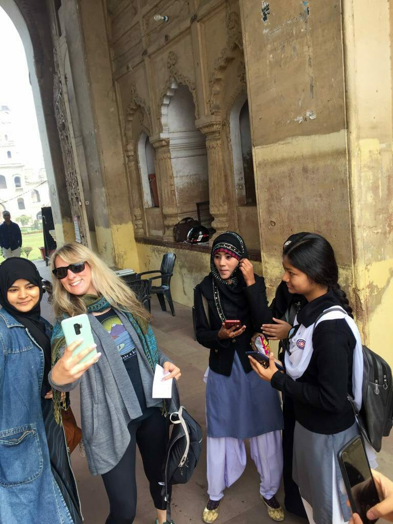 Blonde white woman taking photos with Indian women under a tunnel